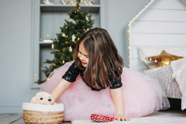 Menina de vestido bonito com cachorro brinquedo no quarto de cama na árvore de natal