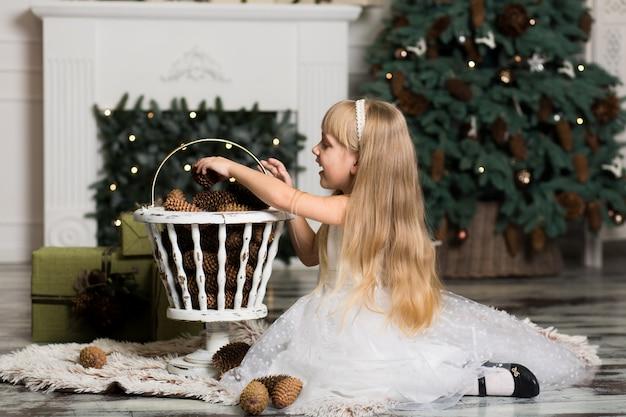 Menina de vestido branco brinca com pinhas em decorações de natal