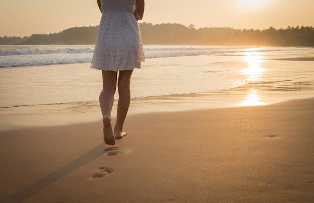 Menina de vestido branco caminhando ao longo da praia do oceano. vista das pernas e pés descalços.