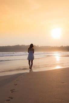 Menina de vestido branco caminhando ao longo da praia do oceano.