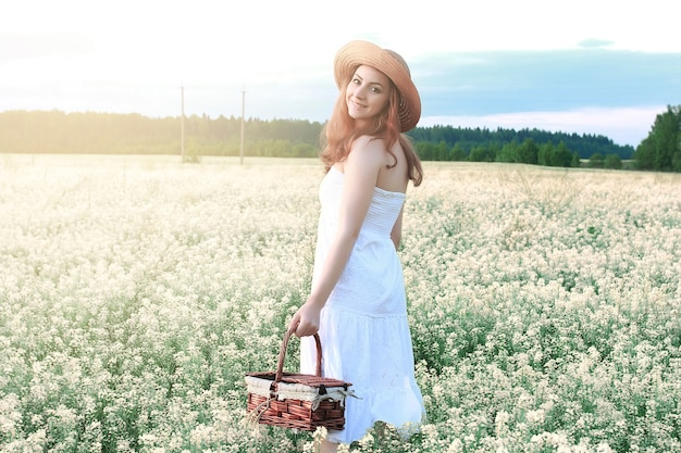 Menina de vestido branco em campo de flores amarelas desabrochando