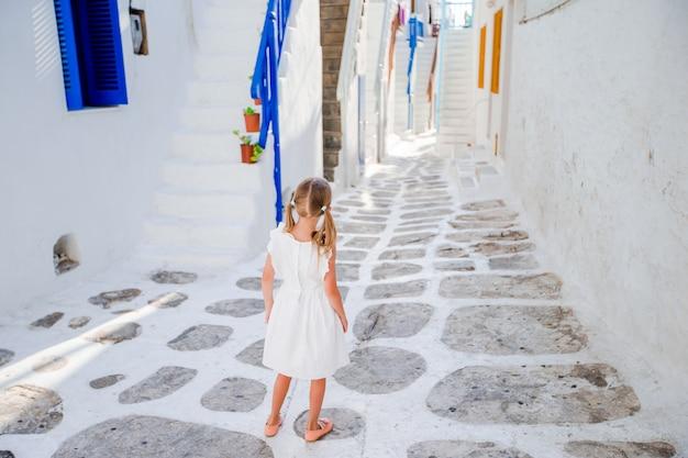 Menina de vestido branco nas ruas antigas de mykonos.
