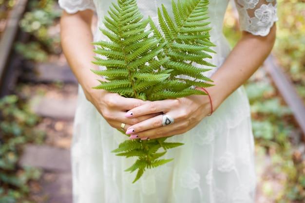 Menina de vestido branco, segurando folhas de samambaia verde na floresta