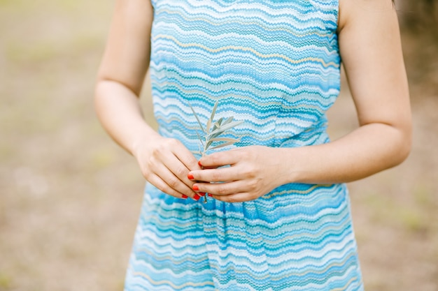 Menina de vestido com um enfeite de ondas do mar segura um raminho verde de uma oliveira nas mãos