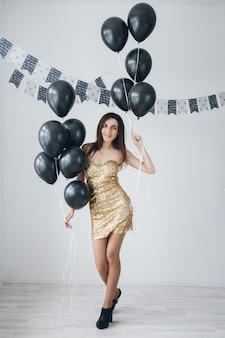 Menina de vestido dourado com balões pretos