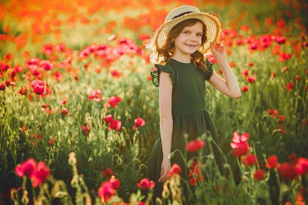 Menina de vestido e chapéu de palha ao ar livre em poppy field no pôr do sol