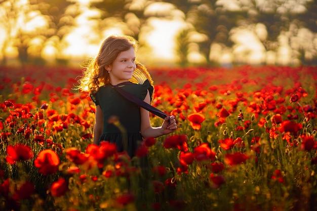 Menina de vestido e chapéu de palha ao ar livre no campo de papoulas