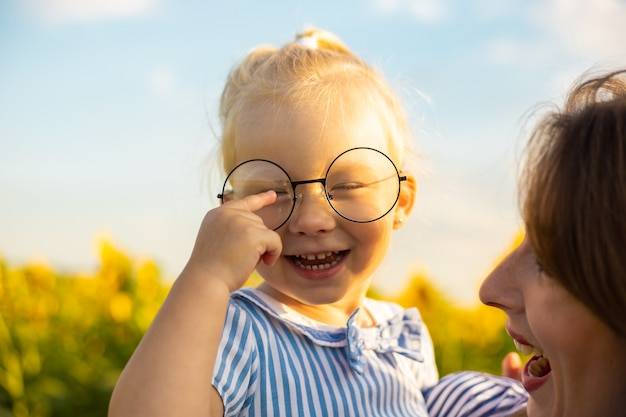 Menina de vestido e óculos nos braços da mãe em um campo de girassol.