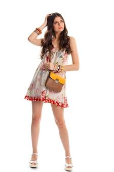 Menina de vestido floral branco. saco marrom e laranja. sandálias e peça de roupa de linho. roupas de verão de design elegante.