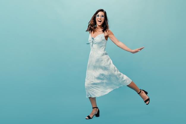 Menina de vestido midi e sandálias pulando sobre fundo azul