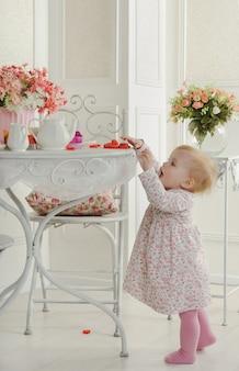 Menina de vestido perto da mesa para o chá, no interior
