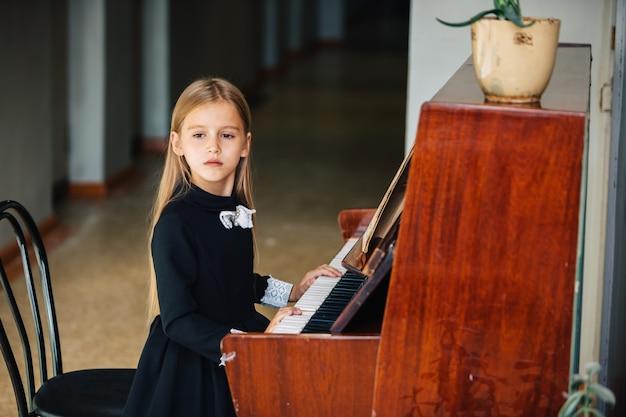 Menina de vestido preto aprende a tocar piano. a criança toca um instrumento musical. colegial, olhando para o lado.