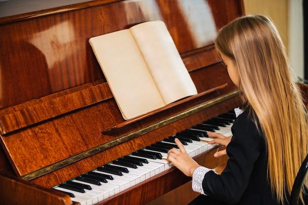 Menina de vestido preto aprende a tocar piano. a criança toca um instrumento musical.