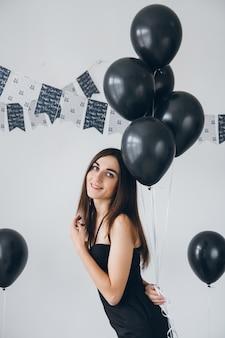 Menina de vestido preto com balões pretos