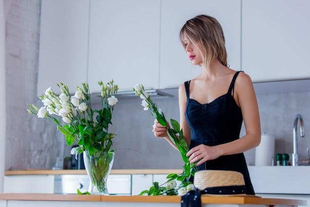 Menina de vestido preto está segurando rosas brancas antes de colocá-los em um vaso