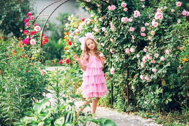 Menina de vestido rosa com um laço na cabeça no jardim de rosas. boneca menina