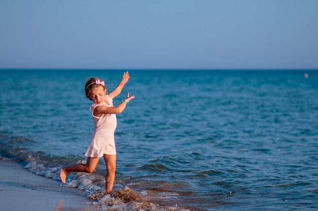 Menina de vestido rosa correndo na praia ao pôr do sol.