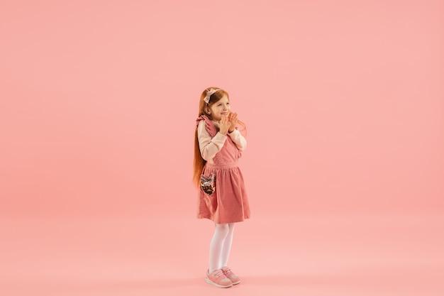 Menina de vestido rosa na parede rosa