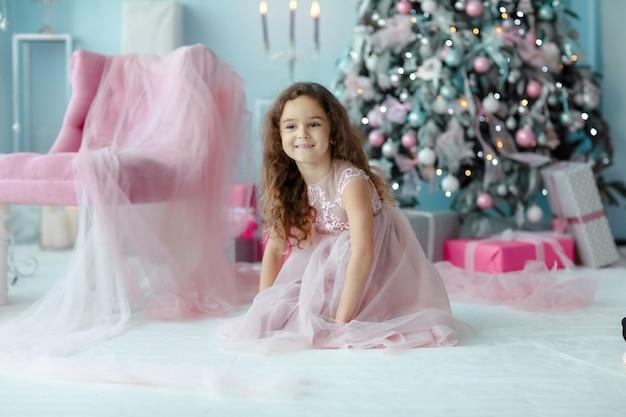 Menina de vestido rosa rastejando perto de uma árvore de natal