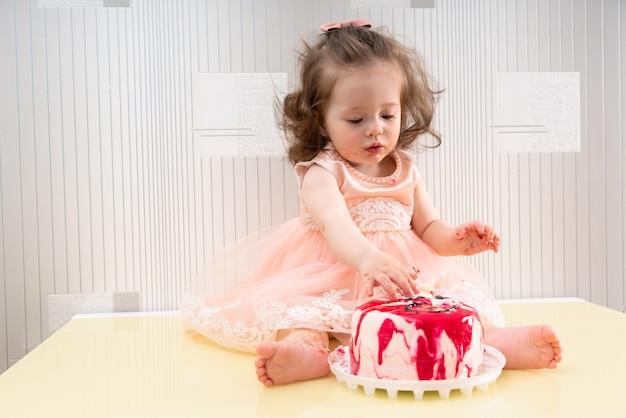 Menina de vestido rosa sentada na superfície da mesa e comendo bolo