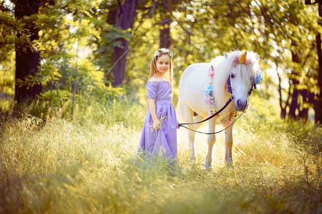 Menina de vestido roxo abraçando o cavalo unicórnio branco.