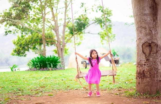 Menina de vestido sentado em um balanço no parque