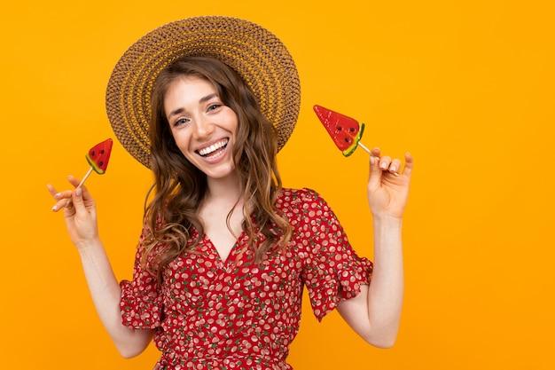 Menina de vestido vermelho e chapéu em um fundo amarelo com um sorriso largo e pirulitos nas mãos dela