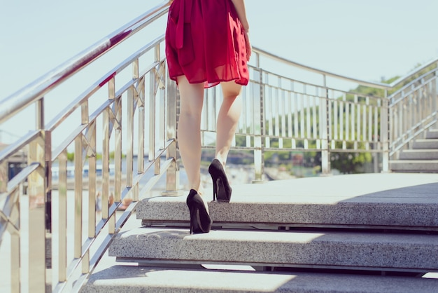 Menina de vestido vermelho e salto alto subindo escadas