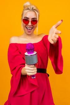 Menina de vestido vermelho elegante com ombros nus com óculos retrô detém um microfone e canta