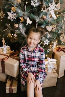 Menina de vestido xadrez, sentado perto de árvore de natal em presentes