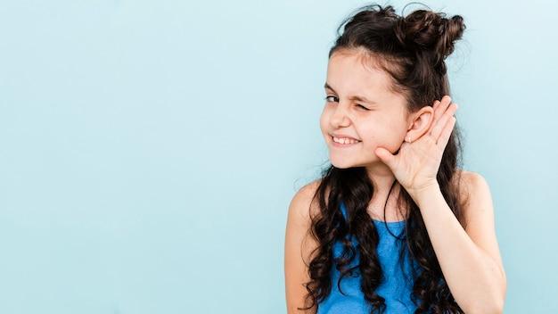 Menina de vista frontal escolhendo com pose de orelha