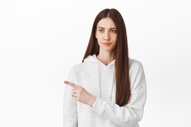 Menina decepcionada com uma careta, olhando para algo estúpido ou idiota, julgando um texto promocional ruim, apontando para o lado no espaço esquerdo da cópia, não gosta de fazer uma careta, em pé sobre uma parede branca