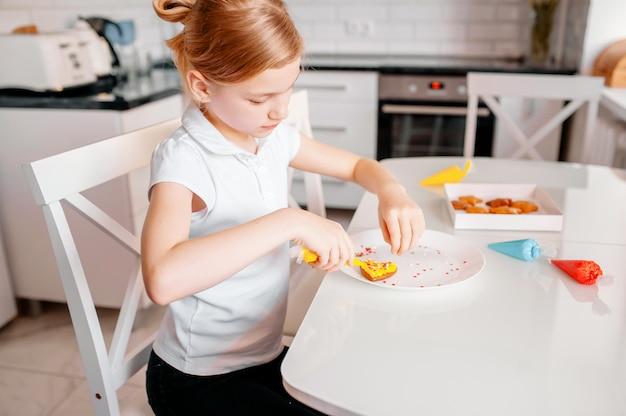 Menina decora biscoito em forma de coração de gengibre com glacê de cor.