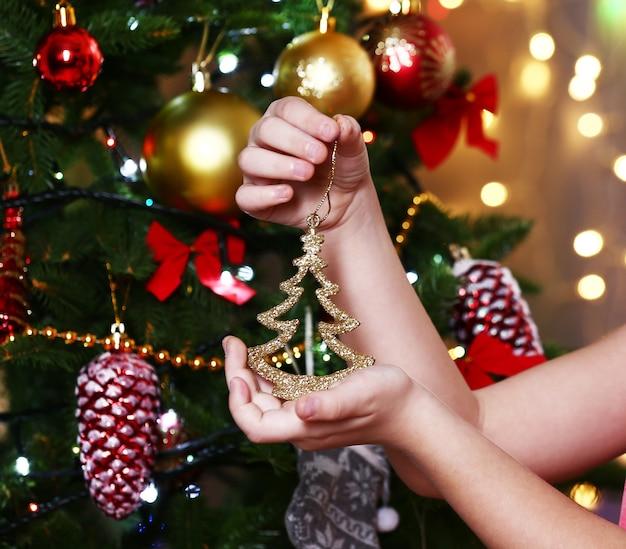 Menina decorando a árvore de natal em um fundo brilhante