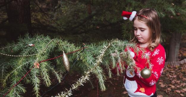 . menina, decorar a árvore de natal ao ar livre no quintal da casa antes das férias