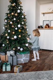 Menina decorar a árvore de natal dentro de casa