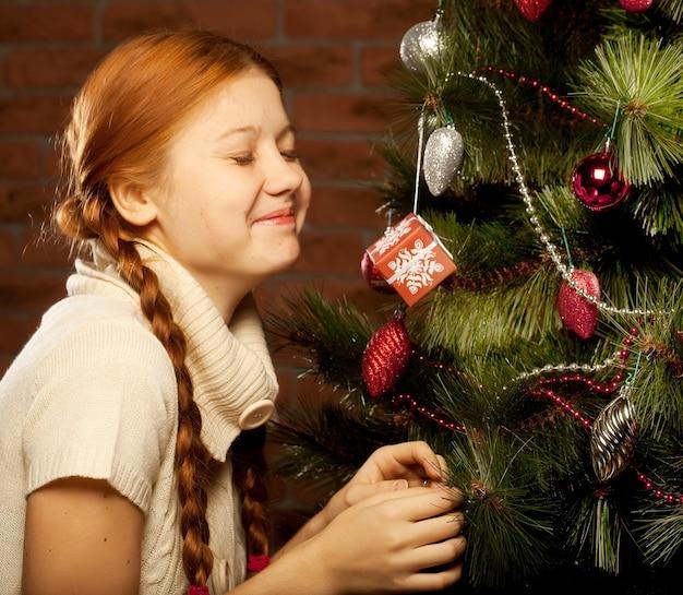 Menina decorar a árvore de natal