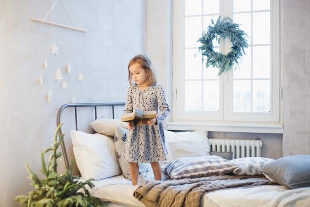Menina, decorar a casa com árvore de natal e decoração de natal.