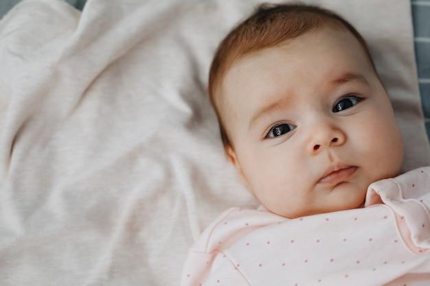 Menina deitada de costas na cama em um quarto brilhante, vestido com um vestido leve. calma bebê bebê 3 meses de idade. copie o espaço