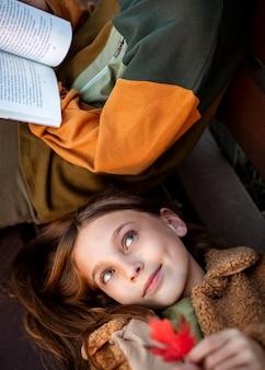 Menina deitada em um banco enquanto sua amiga está lendo