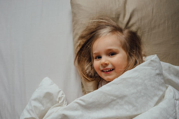 Menina deitada na cama coberta com um cobertor em casa pela manhã acorda no quarto