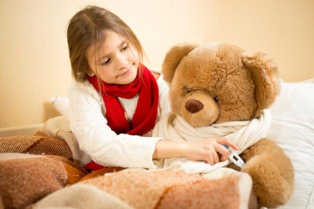 Menina deitada na cama medindo a temperatura do urso de pelúcia com termômetro