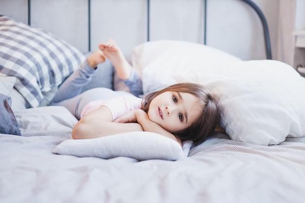 Menina deitada na cama, menina descansando entre os travesseiros e cobertores, sonhos