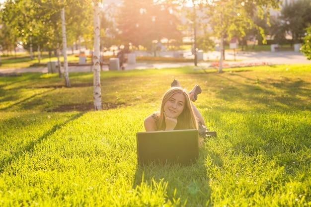 Menina deitada na grama com um laptop