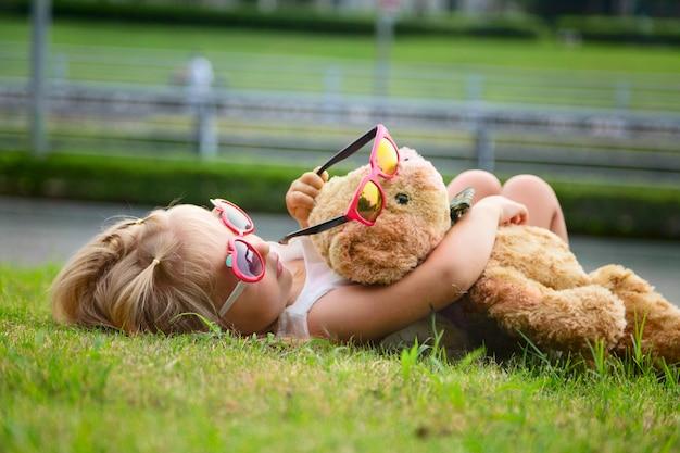 Menina deitada na grama e abraçando um ursinho de pelúcia