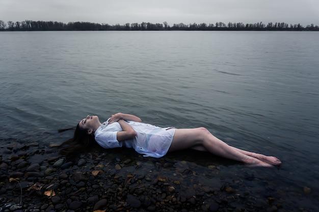 Menina deitada na rocha de um rio escuro. ofélia conceitual