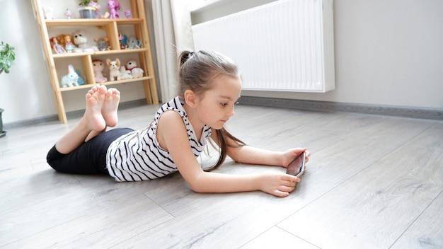 Menina deitada no chão de madeira com um telefone, assistindo um desenho animado ou fazendo uma chamada de vídeo