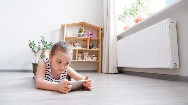 Menina deitada no chão de madeira com um telefone