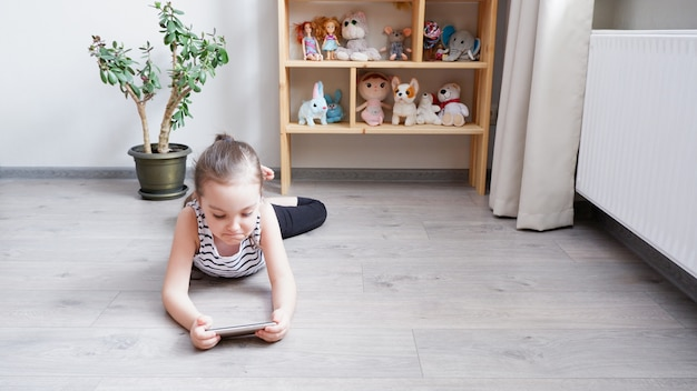 Menina deitada no chão de madeira, fazendo uma chamada de vídeo