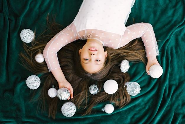 Menina deitada no chão em um cobertor, bolas brancas de natal, ao lado da árvore de natal, vista de cima, conceito de ano novo